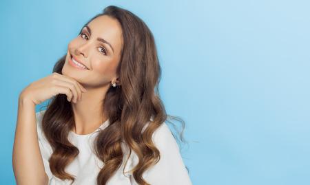 donne eleganti: Donna sorridente con i capelli lunghi su sfondo azzurro. Moda e bellezza concetto in studio.