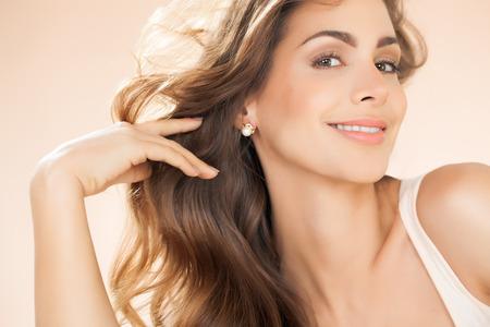 bellezza: Bella donna sorridente con capelli e perle lunghi orecchini. Moda e bellezza concetto in studio.