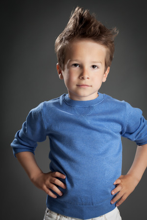 five year old: Cute serious five year old boy posing in studio over grey background. Stock Photo
