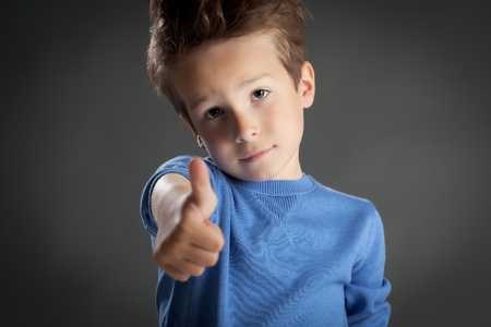 5 6 years: Cute five year old boy posing in studio over grey background. Thumbs up gesture. Stock Photo