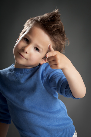 five year old: Cute five year old boy posing in studio over grey background.