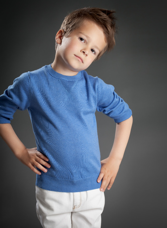 five year old: Serious five year old boy posing in studio over grey background. Stock Photo