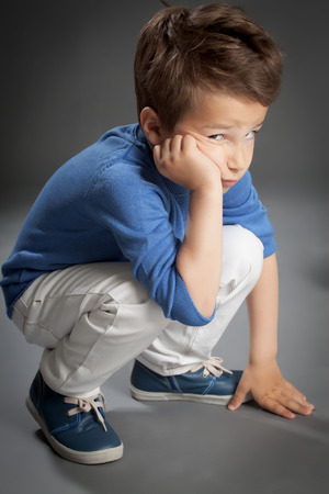 5 years: Cute sad five year old boy posing in studio over grey background with hand cheek.