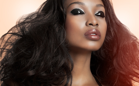 ベージュの背景の上の巨大な髪と美しい濃いモデル。ファッションと美容モデルではアフリカ系の褐色肌。 写真素材