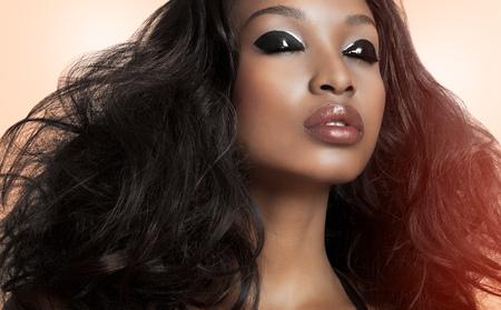 Mooie donkere model met grote haren over beige achtergrond. Mode en beauty met Afrikaanse donkere huid model. Stockfoto