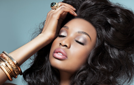 capelli lunghi: Bello modello scuro con gioielli d'oro su sfondo azzurro. Moda e bellezza con il modello di pelle scura africano.