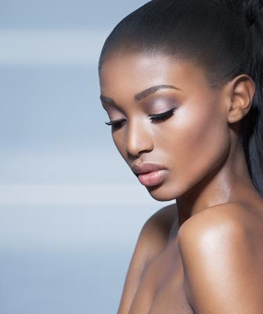 Modelo africano hermoso sobre fondo azul. La moda y la belleza con el modelo de piel oscura de África.