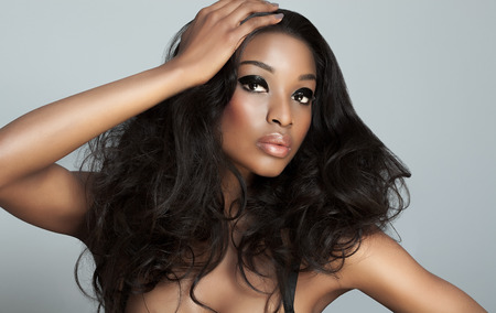 Beautiful dark model with big hair over gray background. Fashion and beauty with African dark skin model. Stock Photo