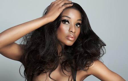 donne eleganti: Bello modello scuro con grandi capelli su sfondo grigio. Moda e bellezza con il modello di pelle scura africano. Archivio Fotografico