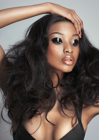 lush: Beautiful dark model with big hair over gray background. Fashion and beauty with African dark skin model. Stock Photo