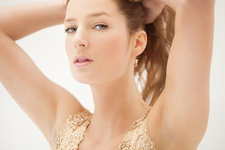 rubia ojos azules: elegante mujer joven hermosa con la parte superior del brillo y pendientes de oro. Foto de archivo
