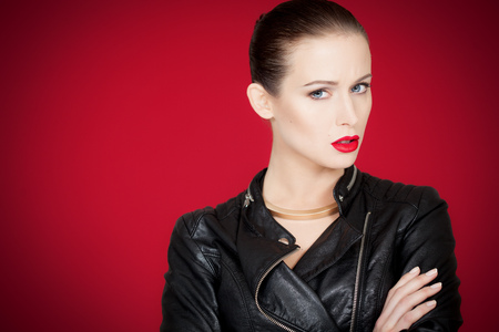 bossy: Confident bossy woman with fashion makeup over red background.