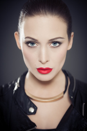 to face to face: Classic portrait of woman with bright red lipstick wearing black leather jacket. Stock Photo