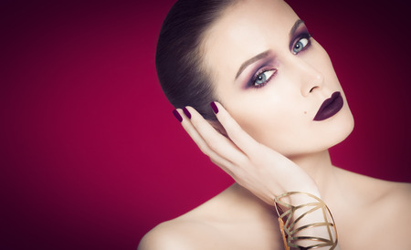 dark blue: Dramatic beautiful woman with sleek heavy makeup, dark purple lipstick and eyeshadow over dark red background. Large golden bracelet and hand touching face.