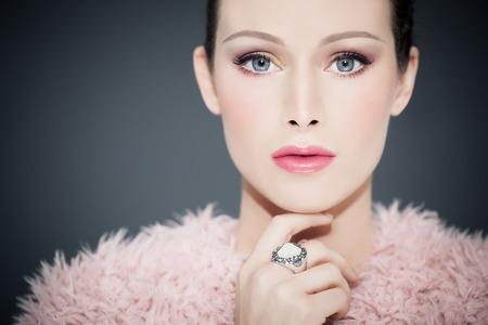Doll-wie schöne Frau mit großen blauen Augen großen weißen Silber Aussage Ring und gefälschte rosa Pelzjacke trägt.
