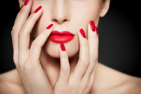 bright lipstick: Closeup of face and hands with beautiful manicure and red glossy polish and matte red lipstick. Stock Photo