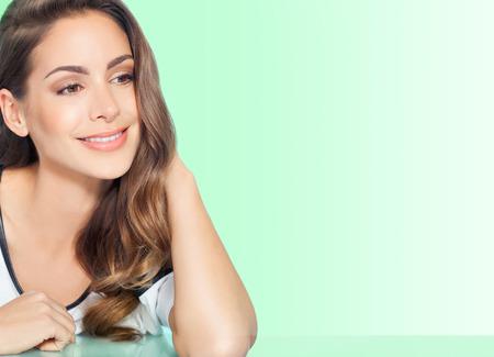 Belle jeune femme souriante avec de longs cheveux sur fond vert. Banque d'images - 52899727