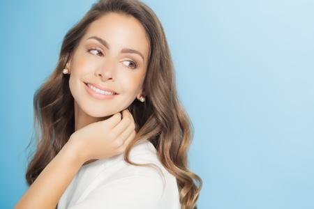 Mooie lachende jonge vrouw met lang haar over blauwe achtergrond.