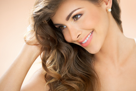 pearl background: Beautiful smiling young woman with long hair and pearl earrings studs over warm beige background.