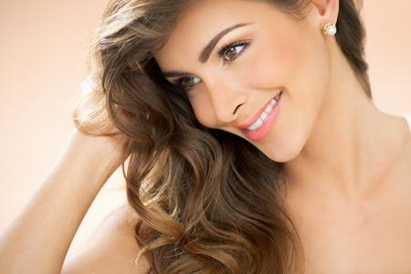 aretes: mujer joven sonriente con pelo pendientes de perlas y espárragos largos sobre el fondo de color beige cálido.