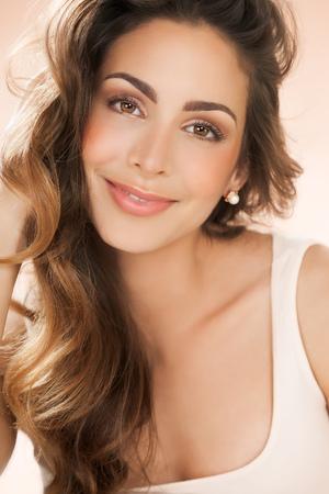 長い髪と温かみのあるベージュの背景の上の真珠のイヤリング スタッドの美しい笑顔の若い女性。