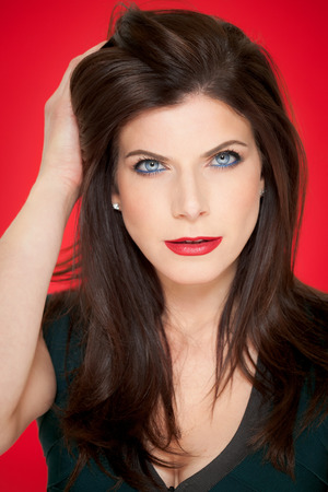 dark hair: Beautiful elegant Caucasian woman with long dark hair posing with classic red lipstick over red background.