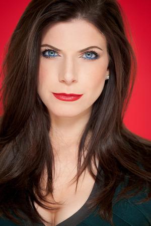 ojos negros: La mujer caucásica elegante hermosa con el pelo largo y oscuro que presenta con el lápiz labial rojo clásico sobre fondo rojo.