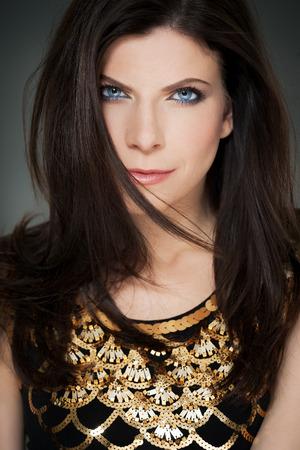 black hair blue eyes: Modern elegant Caucasian woman with golden top wearing soft makeup.