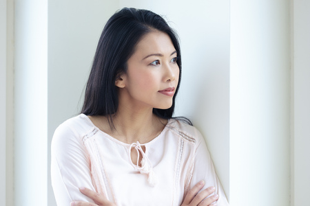 looking out: Pensive Asian woman standing at window looking out with contemplating expression.