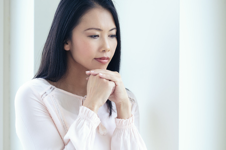 Pensive Asian woman standing at window looking out with contemplating expression.