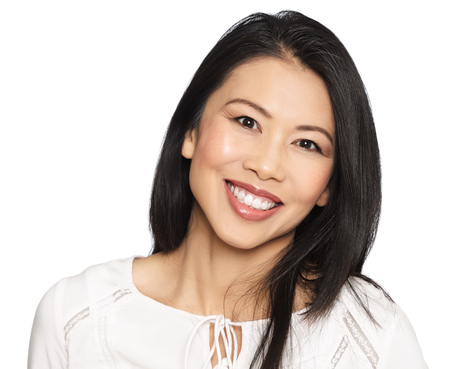 Enthousiastic happy smilng attractive casual thirty to forty year old Asian woman posing in studio.