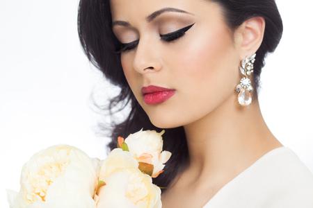 Studio portrait d'une belle jeune femme avec une peau bronzée, cheveux longs style et agréable maquillage. Banque d'images