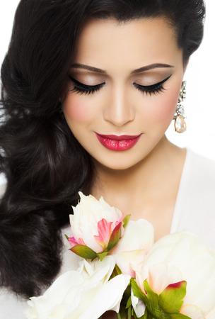 mujer con rosas: Retrato del estudio de una mujer joven y hermosa con la piel bronceada, cabello largo estilo y buen maquillaje.