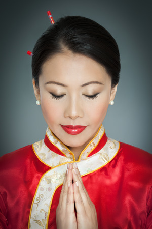 meditaion: Portrait of Asian woman in traditional red silk gown praying with closed eyes in studio. Stock Photo