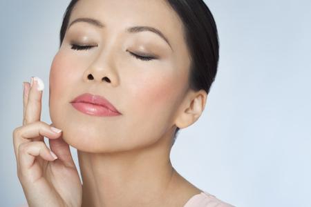 Gros plan de belle femme asiatique avec une peau éclatante de plus de trente application de la crème de soins du visage avec les yeux fermés. Banque d'images - 56391729