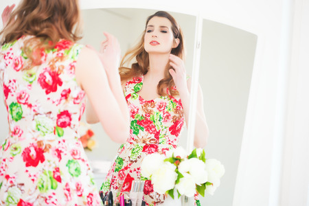 Young Caucasian woman getting ready before vanity mirror in retro floral summer dress.