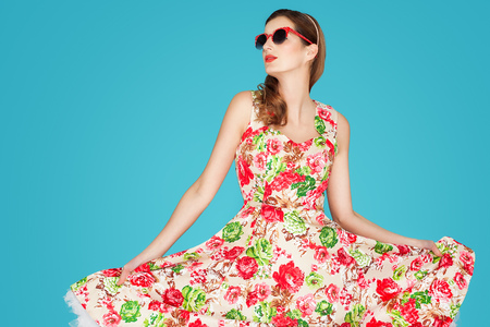 Young Caucasian woman in retro floral summer dress over blue background.
