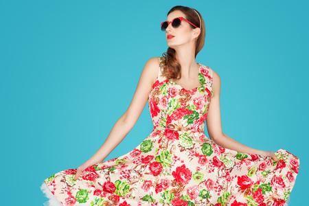Młoda kobieta Caucasion retro kwiatowy letni strój na niebieskim tle.