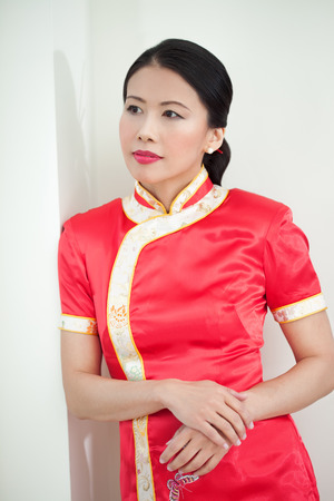 30 40: Traditional Chinese woman posing indoor wearing festive red silk robe.