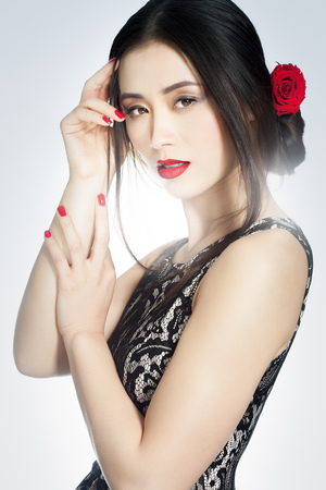 white rose: Beautiful Asian fashion model wearing lace dress, red nail polish and lipstick and red rose in hairstyle. Stock Photo