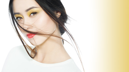lips glow: Beautiful Asian woman with colorful soft makeup with yellow and orange tones.