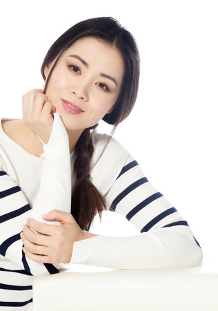 asian natural: Natural Asian girl with braid and striped pullover posing over white background.
