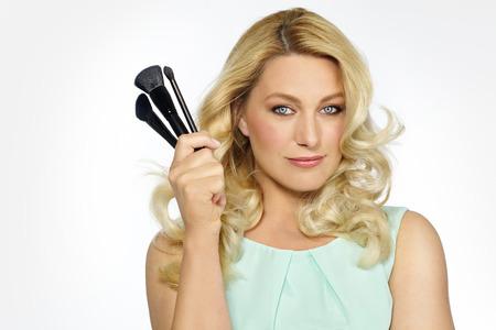 ojos verdes: Portrit de maquillaje artista mujer que sostiene threen selección pinceles de maquillaje.
