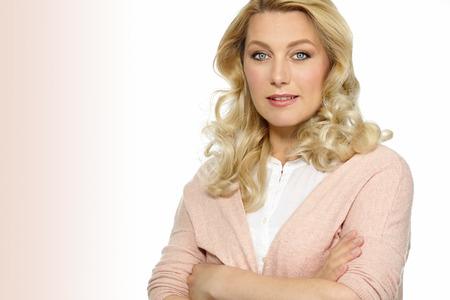 ojos azules: Retrato de la hermosa mujer de raza caucásica treinta años de edad en una blusa blanca y un chaleco de color rosa con los brazos cruzados. Foto de archivo