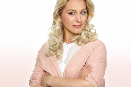 thirty: Portrait of beautiful Caucasian thirty year old woman in white blouse and pink vest with arms crossed. Stock Photo