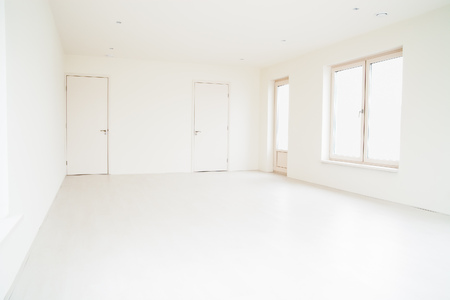 empty room background: Empty off-white room with large windows and light wooden floor. Stock Photo