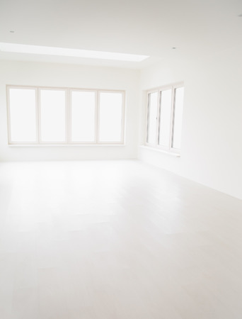 white window: Empty off-white room with large windows and light wooden floor. Stock Photo