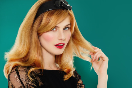 Beautiful woman with red lipstick and beautiful styled red hair on cyan background. Beautiful woman with copyspace.
