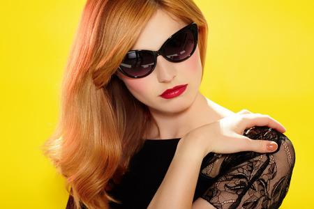 amarillo y negro: Modelo de manera con las gafas de sol retro y lápiz labial rojo sobre fondo amarillo. Mujer hermosa con el copyspace.