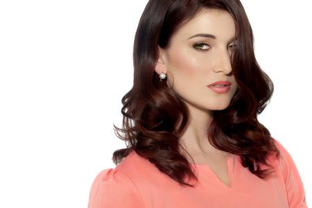 ojos marrones: Retrato aislado de la hermosa mujer moderna que usa la tapa de color rosa coral.